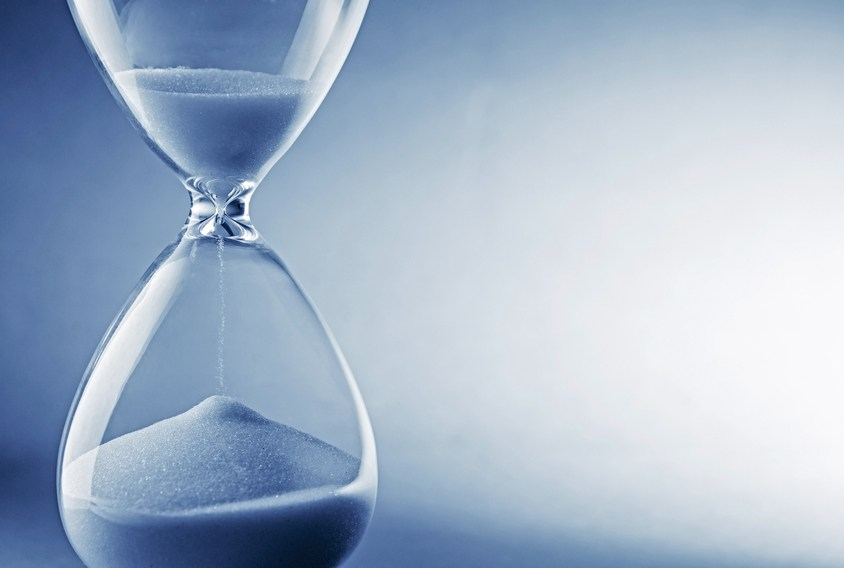 Closeup hourglass clock on light blue background